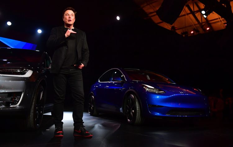 Tesla CEO Elon Musk speaks beside the just unveiled new Tesla Model Y (R) in Hawthorne, California on March 14, 2019. (Photo by Frederic J. BROWN / AFP)        (Photo credit should read FREDERIC J. BROWN/AFP via Getty Images)