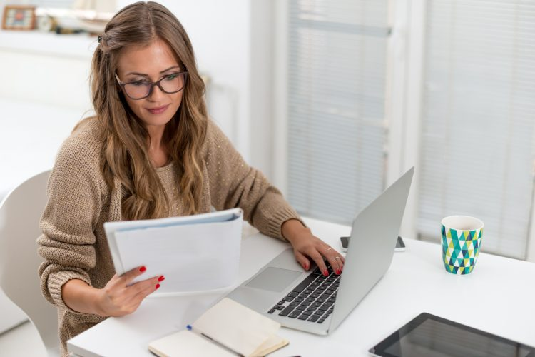 Attractive young woman surfing the net from her home