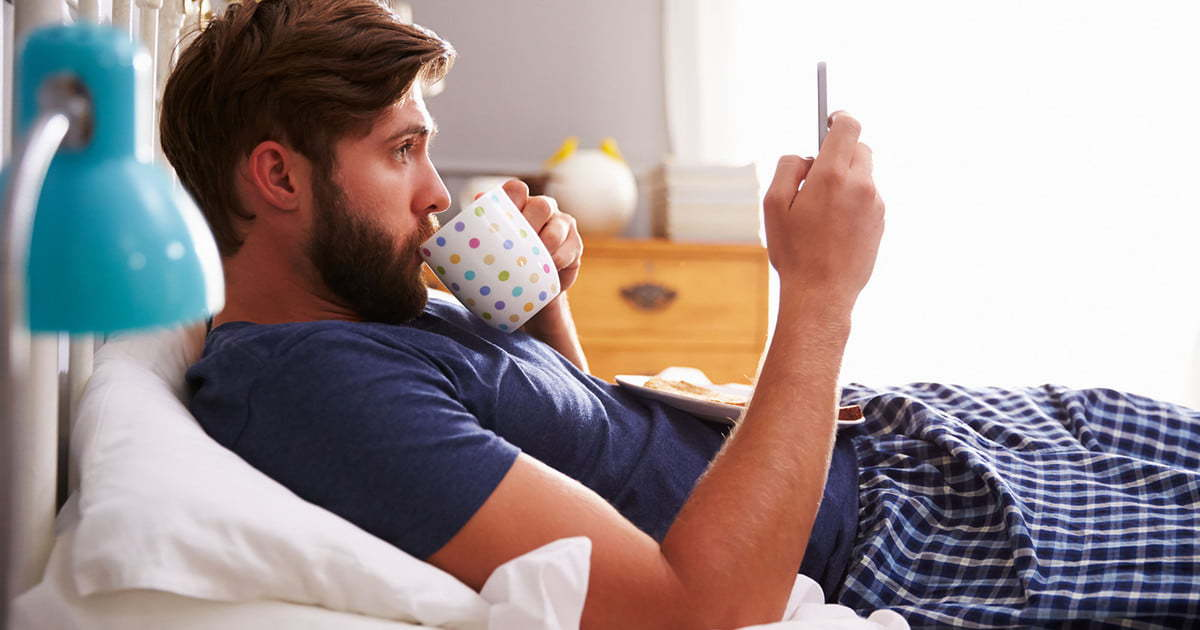 41146717 man eating breakfast in bed whilst using mobile phone 1200x630 c ar1.91